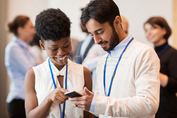 couple with smartphone at business conference Stock photo © dolgachov