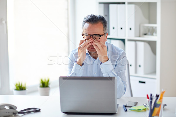 tired businessman in glasses with laptop at office Stock photo © dolgachov