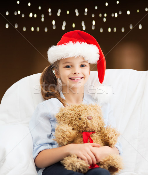 girl in santa hat with teddy bear at christmas Stock photo © dolgachov