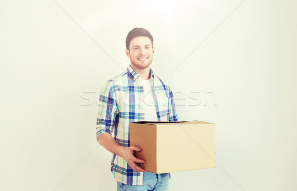 smiling young man with cardboard box at home Stock photo © dolgachov