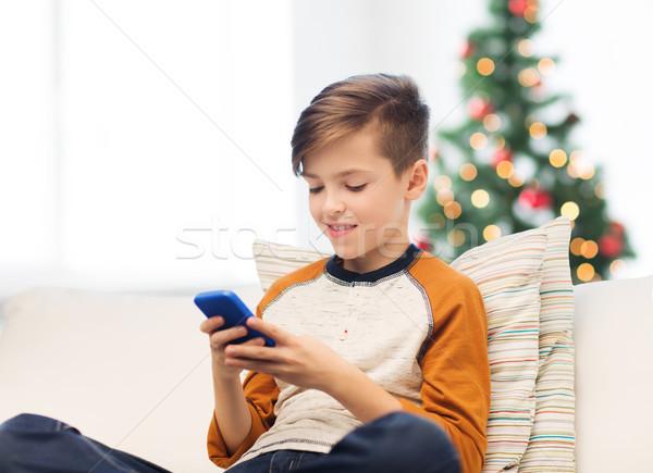 boy playing on smartphone at home at christmas Stock photo © dolgachov