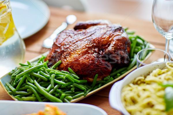 roast chicken with garnish of green peas on table Stock photo © dolgachov