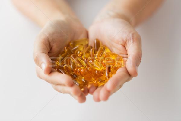 Ręce wątroba oleju kapsułki muzyka Zdjęcia stock © dolgachov