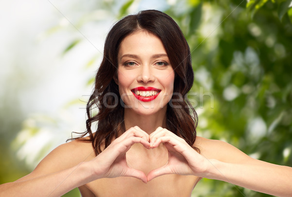 beautiful woman with red lipstick and hand heart Stock photo © dolgachov