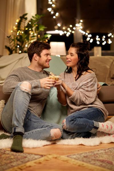 happy couple with gift box at home Stock photo © dolgachov