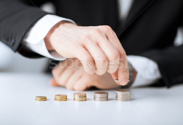 man putting stack of coins into one row Stock photo © dolgachov