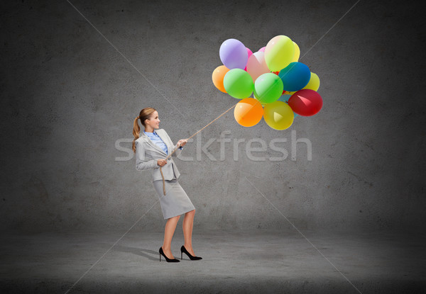 smiling businesswoman pulling rope with balloons Stock photo © dolgachov