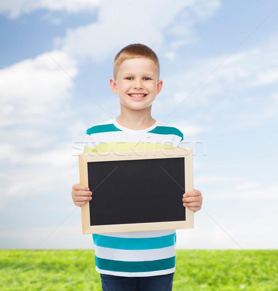 smiling little boy holding blank black chalkboard Stock photo © dolgachov