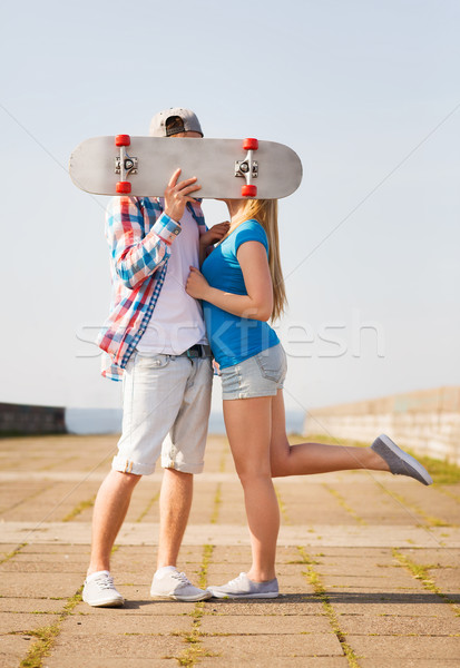 couple with skateboard kissing outdoors Stock photo © dolgachov