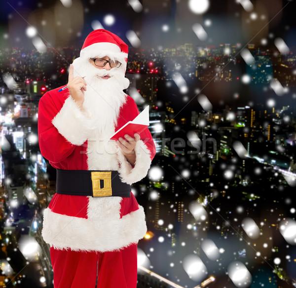 Adam kostüm noel baba notepad Noel tatil Stok fotoğraf © dolgachov
