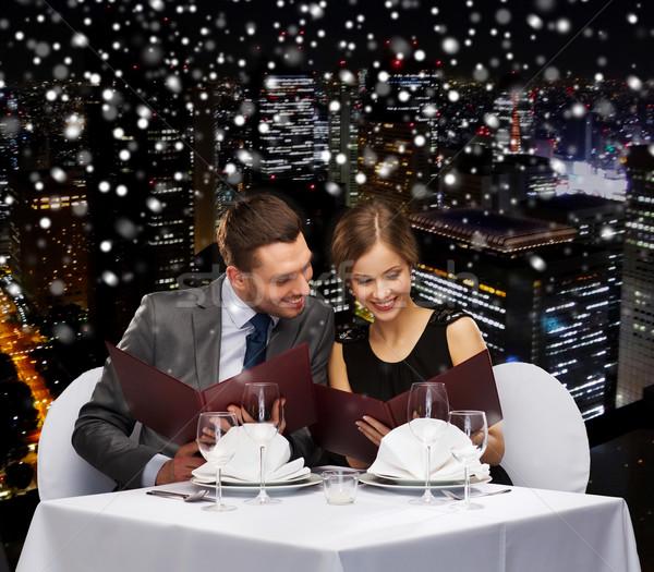 smiling couple with menus at restaurant Stock photo © dolgachov