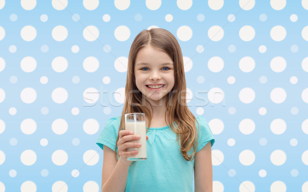 smiling girl with glass of milk over polka dots Stock photo © dolgachov