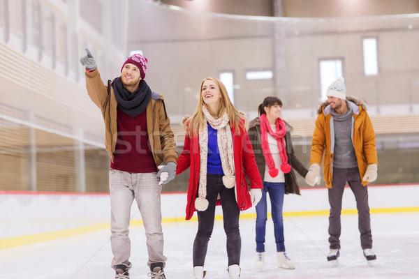 happy friends pointing finger on skating rink Stock photo © dolgachov