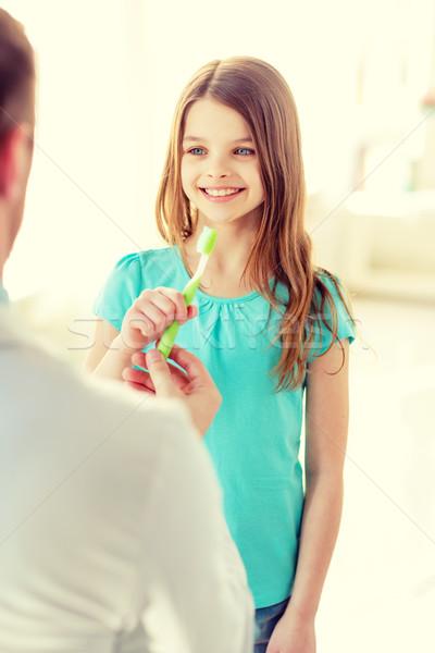 Mannelijke arts tandenborstel glimlachend meisje gezondheidszorg kind Stockfoto © dolgachov