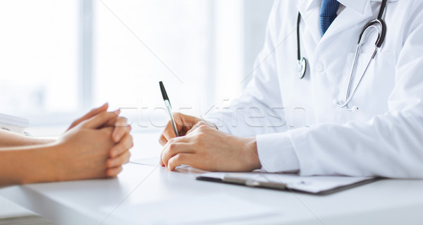patient and doctor taking notes Stock photo © dolgachov