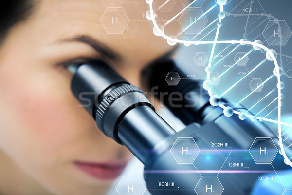 close up of scientist looking to microscope in lab Stock photo © dolgachov