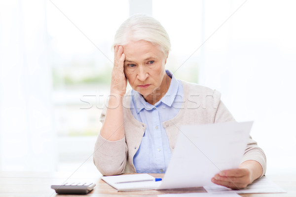 Stock photo: senior woman with papers and calculator at home