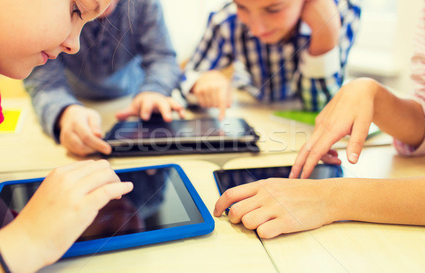 close up of school kids playing with tablet pc  Stock photo © dolgachov