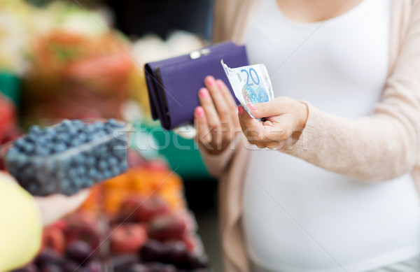 pregnant woman with wallet buying beries at market Stock photo © dolgachov