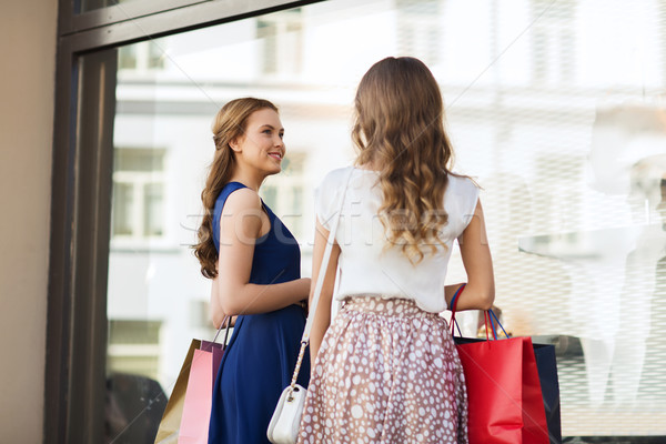 happy women with shopping bags at shop window Stock photo © dolgachov