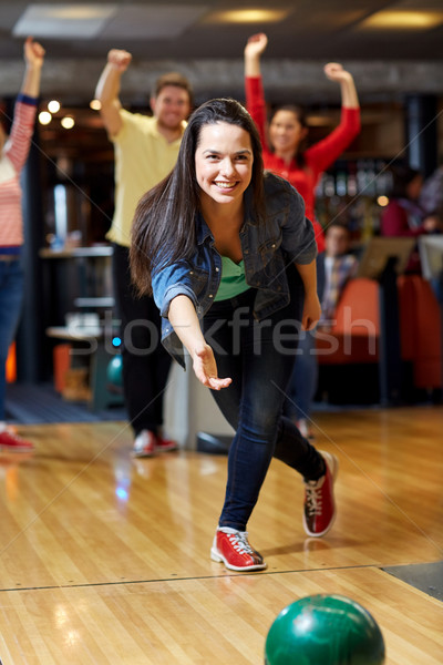 happy young woman throwing ball in bowling club Stock photo © dolgachov