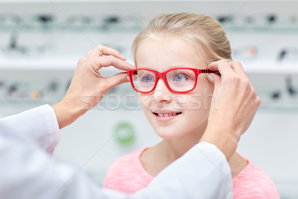 optician putting glasses to girl at optics store Stock photo © dolgachov
