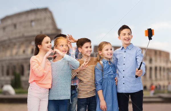 kids with smartphone selfie stick over coliseum Stock photo © dolgachov