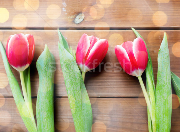 close up of red tulip flowers on wooden table Stock photo © dolgachov