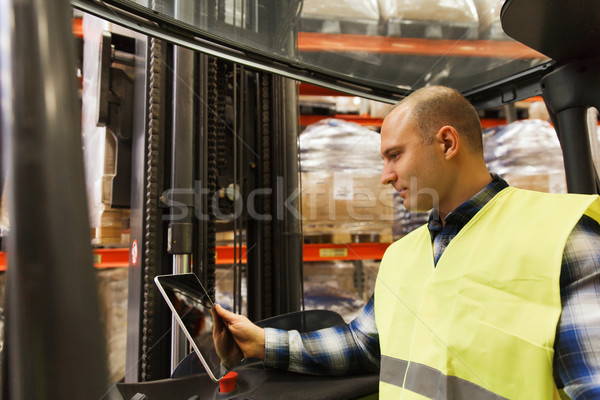 Stock photo: man with tablet pc operating forklift at warehouse