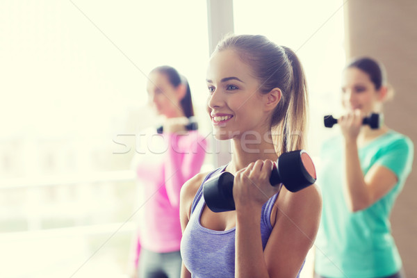 group of happy women with dumbbells in gym Stock photo © dolgachov