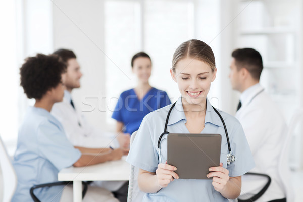 happy doctor with tablet pc over team at clinic Stock photo © dolgachov