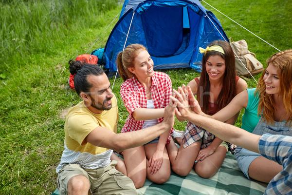 happy friends making high five at camping Stock photo © dolgachov