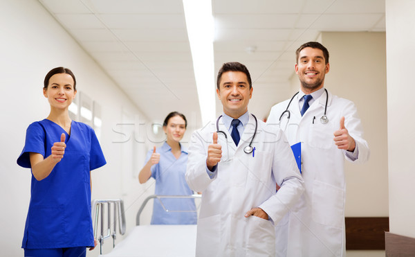Stock photo: happy doctors showing thumbs up at hospital