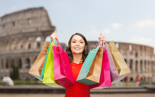 young happy woman with shopping bags over coliseum Stock photo © dolgachov