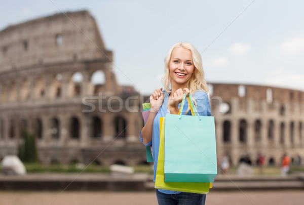 happy woman with shopping bags over coliseum Stock photo © dolgachov
