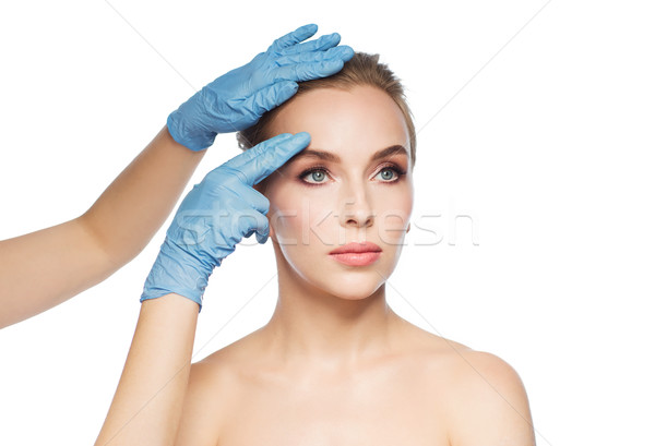 surgeon or beautician hands touching woman face Stock photo © dolgachov