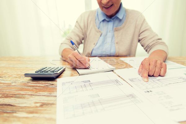 senior woman with papers and calculator at home Stock photo © dolgachov
