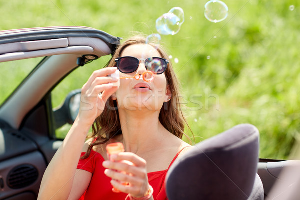 woman blowing bubbles in convertible car Stock photo © dolgachov