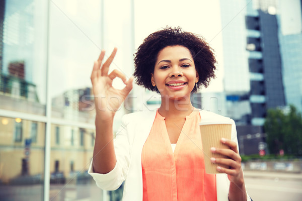 Stock photo: happy woman with coffee showing ok up in city