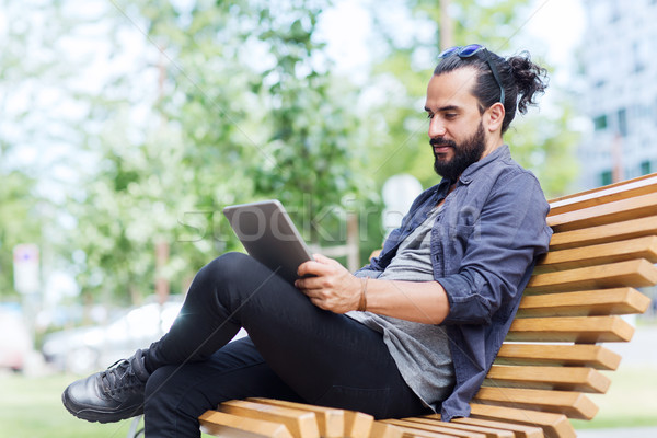 man with tablet pc sitting on city street bench Stock photo © dolgachov