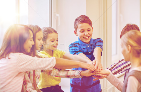 group of smiling school kids putting hands on top Stock photo © dolgachov