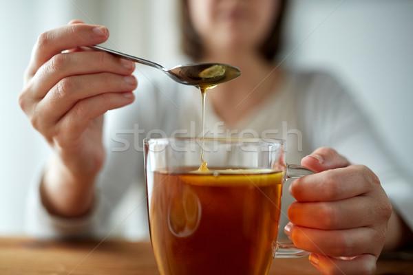 Stock photo: close up of woman adding honey to tea with lemon