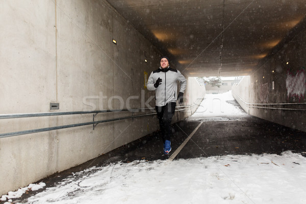 happy man running along subway tunnel in winter Stock photo © dolgachov