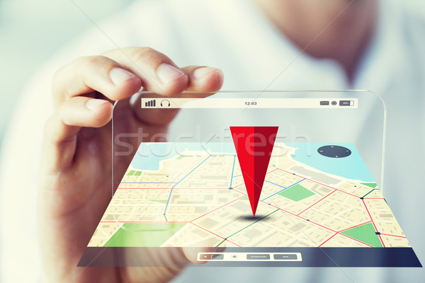 close up of male hand showing smartphone and map Stock photo © dolgachov
