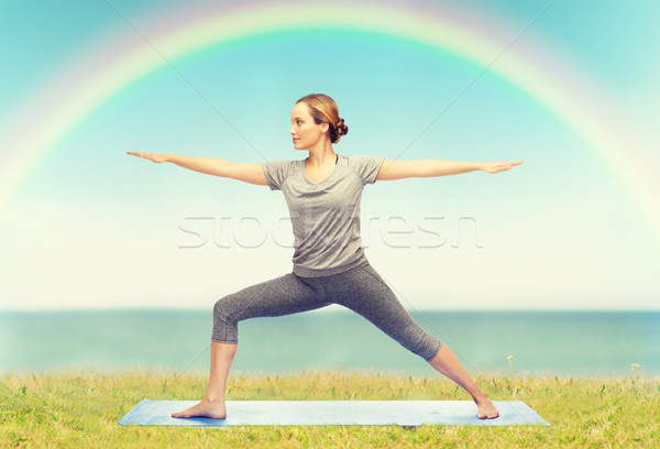 Stock photo: woman making yoga warrior pose on mat