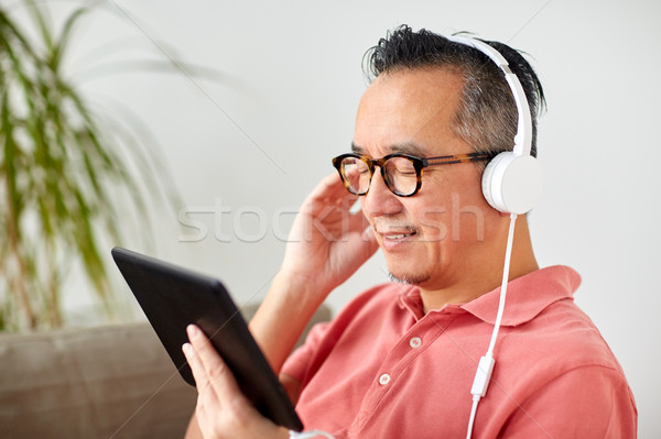 man with tablet pc and headphones at home Stock photo © dolgachov