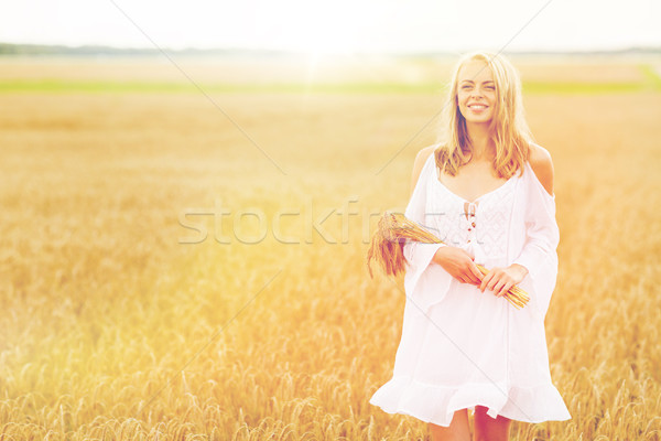 Stock photo: happy young woman with spikelets on cereal field