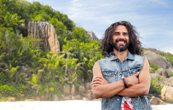 Mosolyog hippi férfi farmer mellény sziget Stock fotó © dolgachov