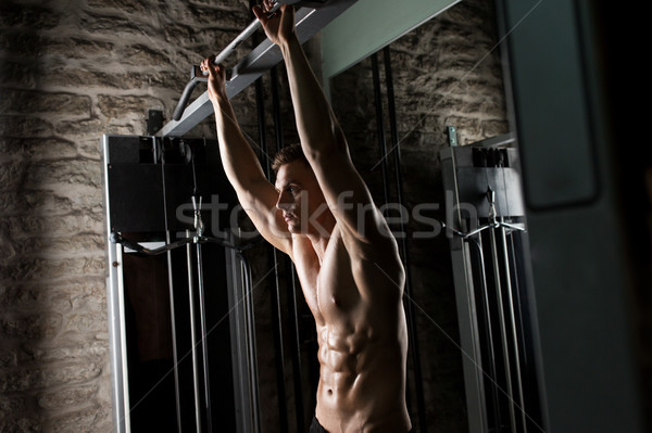 young man exercising with pull-up bar in gym Stock photo © dolgachov