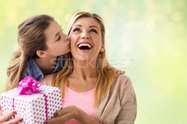 girl giving birthday present to mother over lights Stock photo © dolgachov